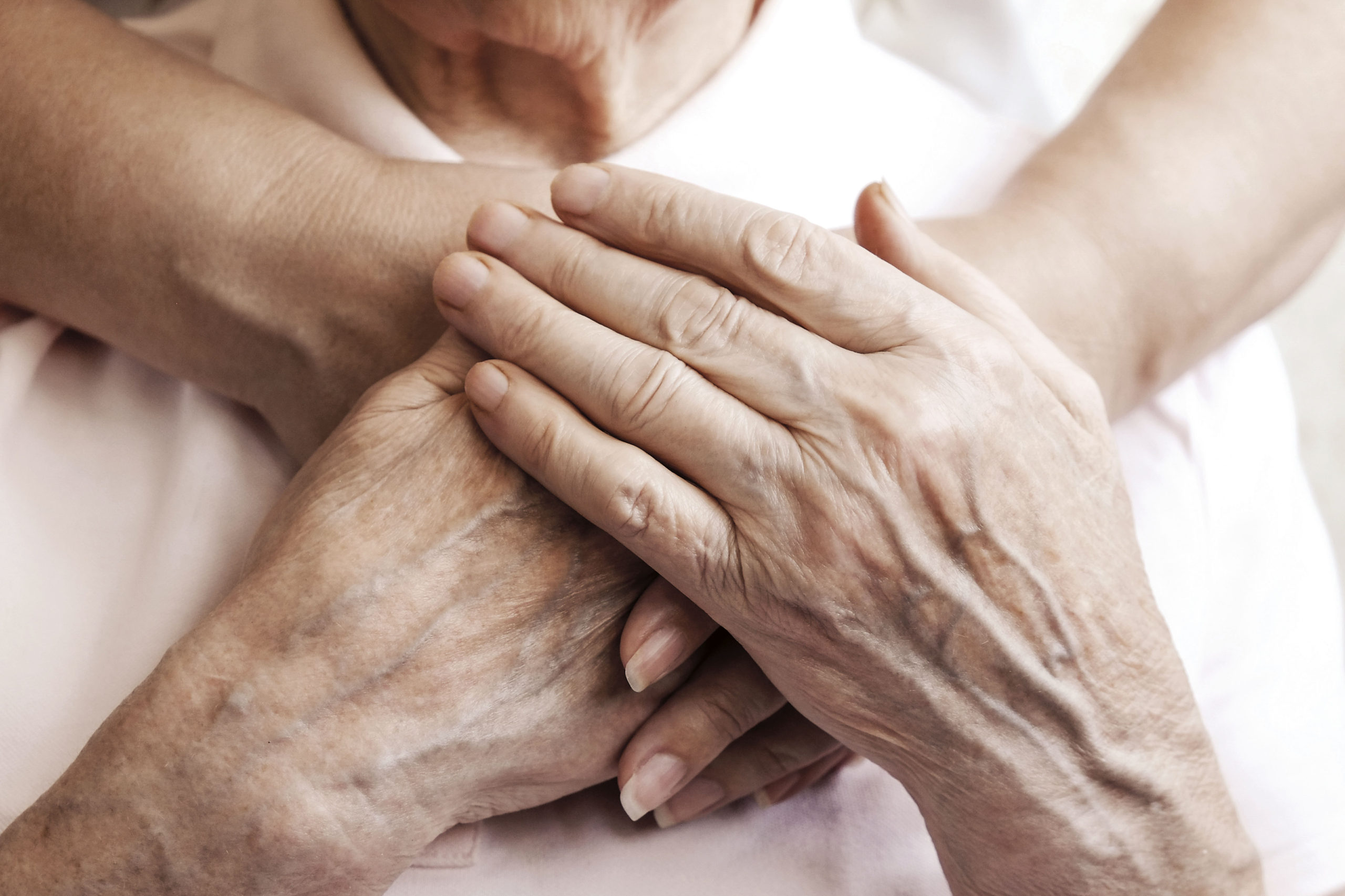 Mature female in elderly care facility gets help from hospital personnel nurse. Senior woman, aged wrinkled skin & hands of her care giver. Grand mother everyday life. Background, copy space, close up