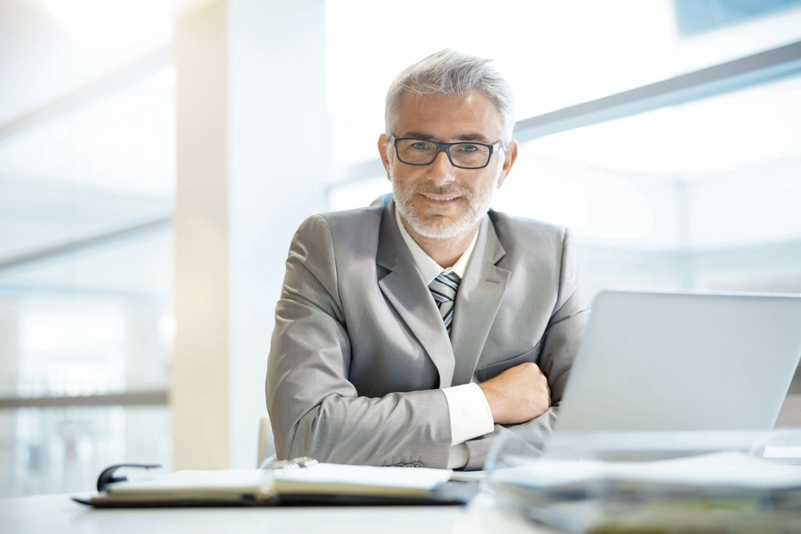 Portrait of mature businessman sitting in office looking at came